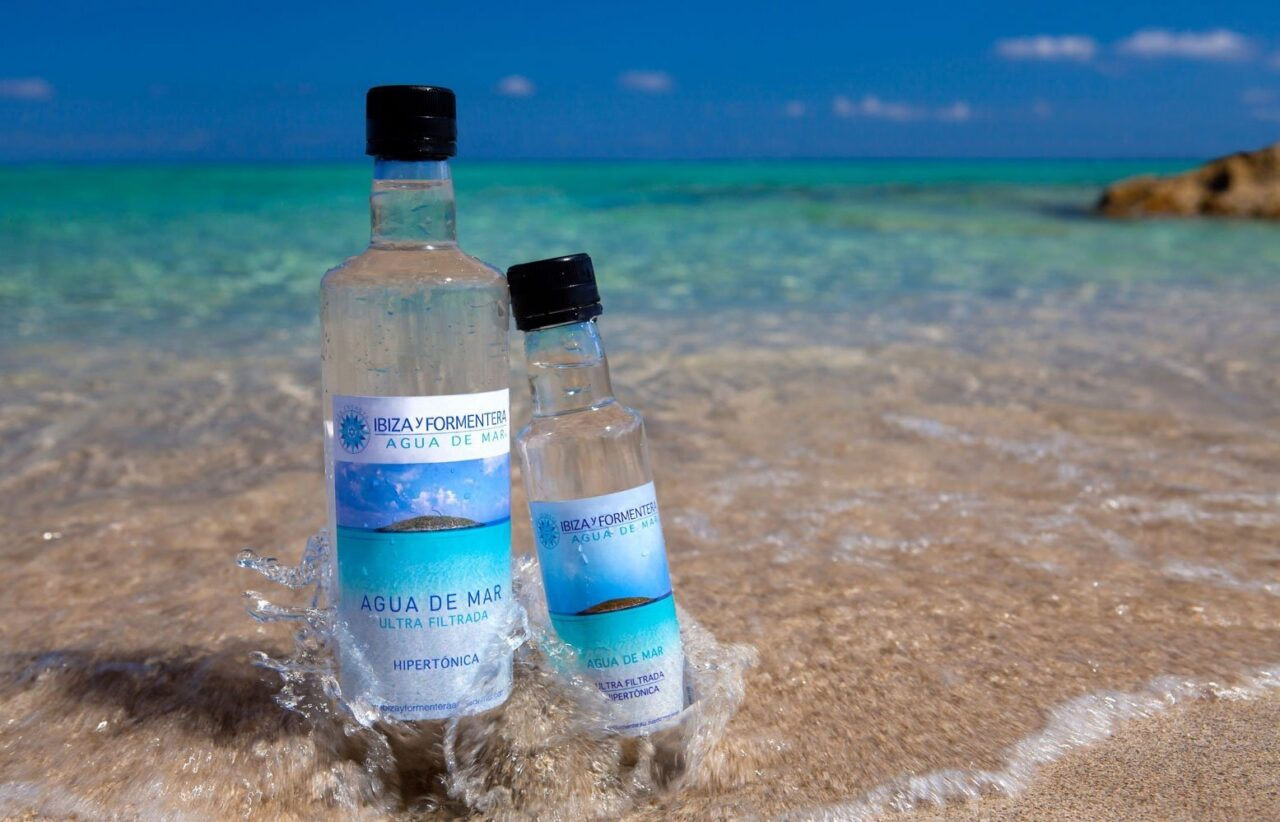 Two bottles of water sitting in the gentle waves of a Mediterranean beach