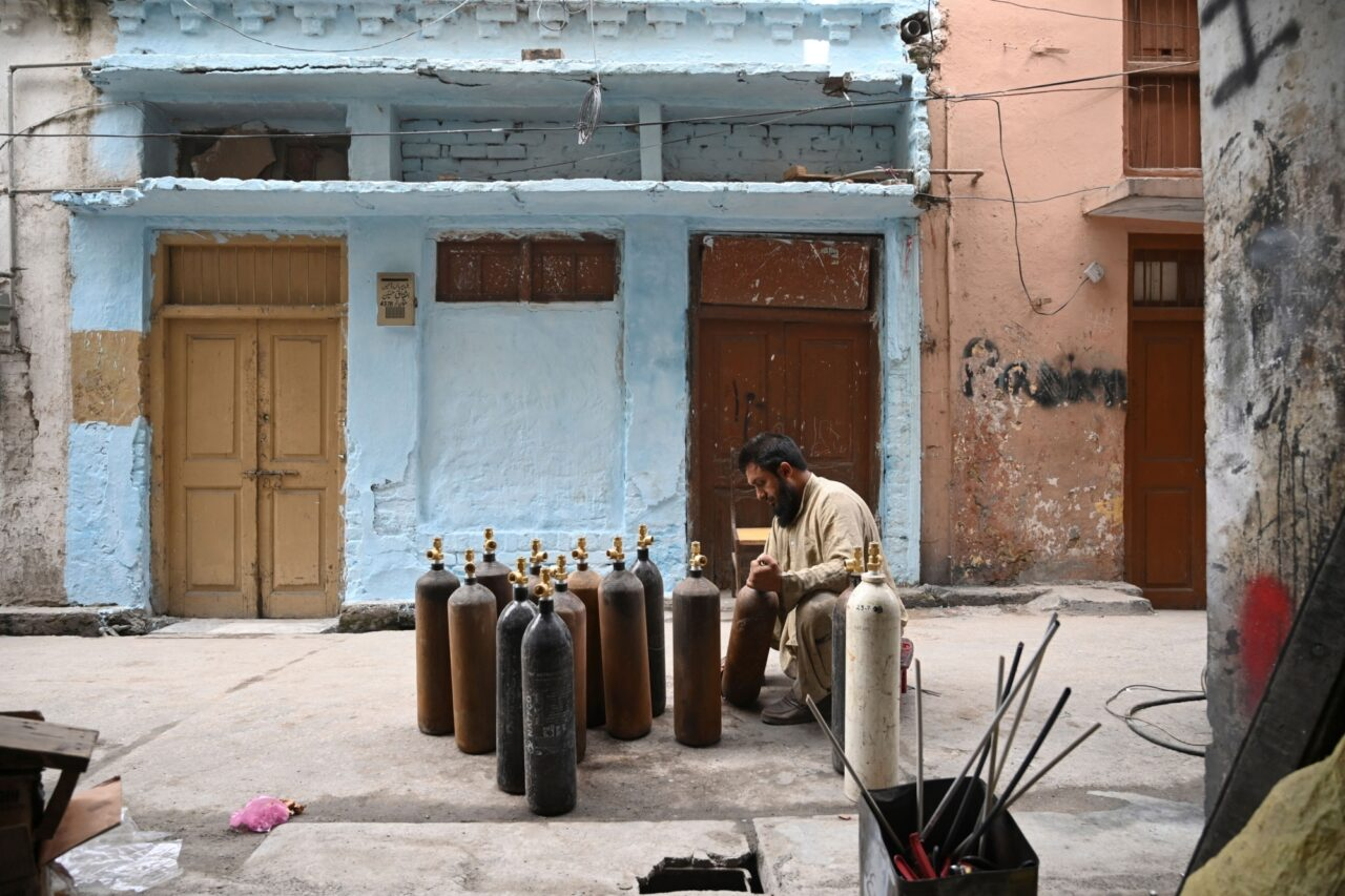 A man kneels in the street cleaning oxygen cylinders