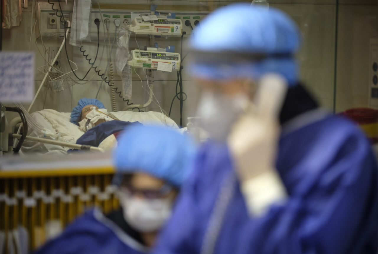 A patient in intensive care and two doctors in scrubs