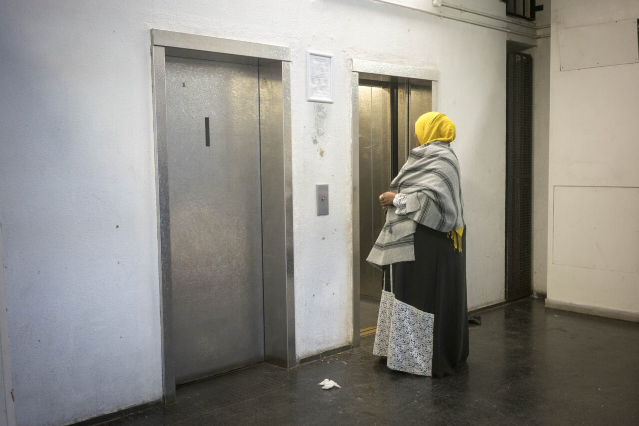 A woman in a yellow headscarf and black and white shawl stands by a bank of lifts on a council estate