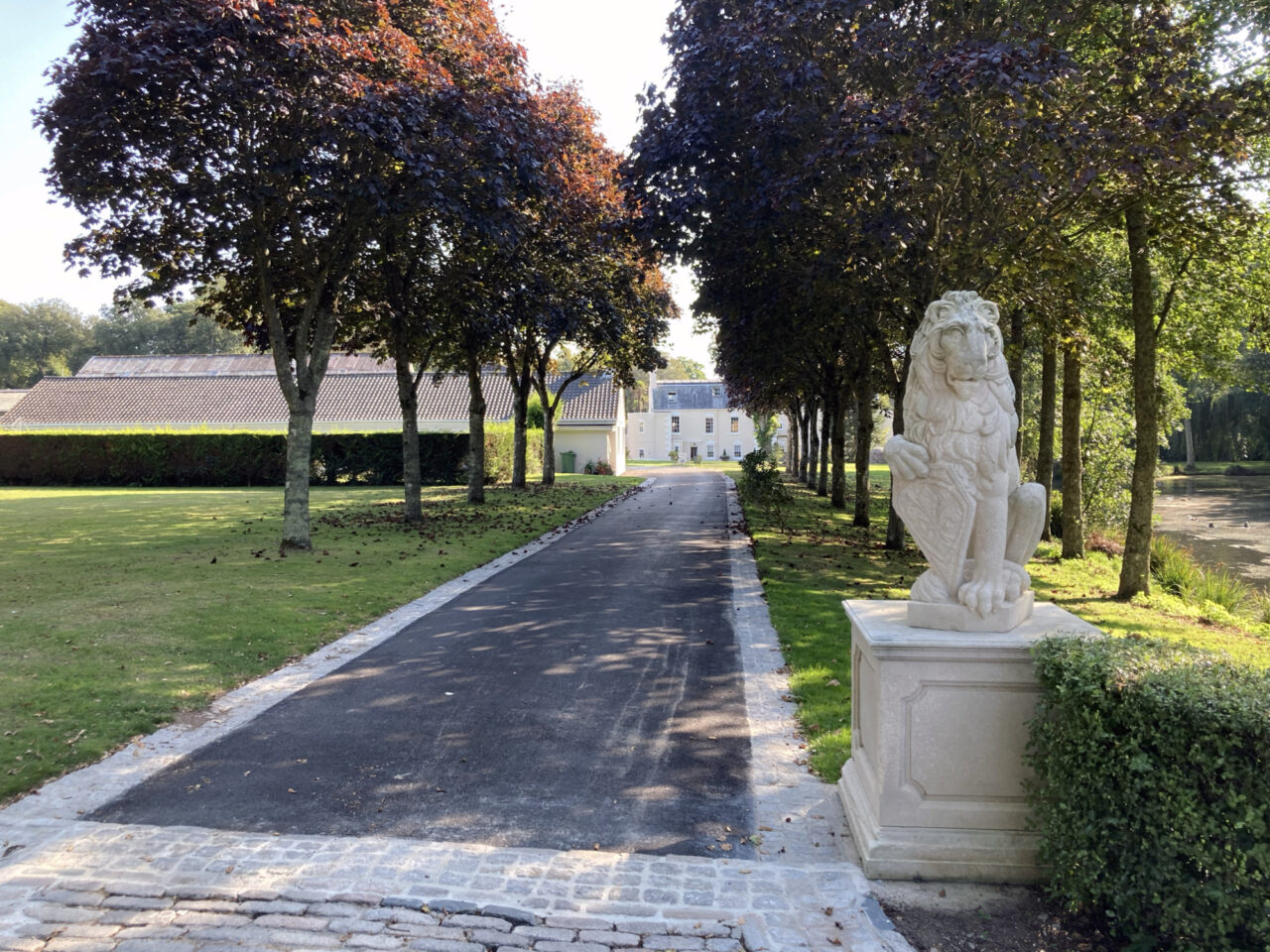The driveway up to the manor, flanked by a lion statue