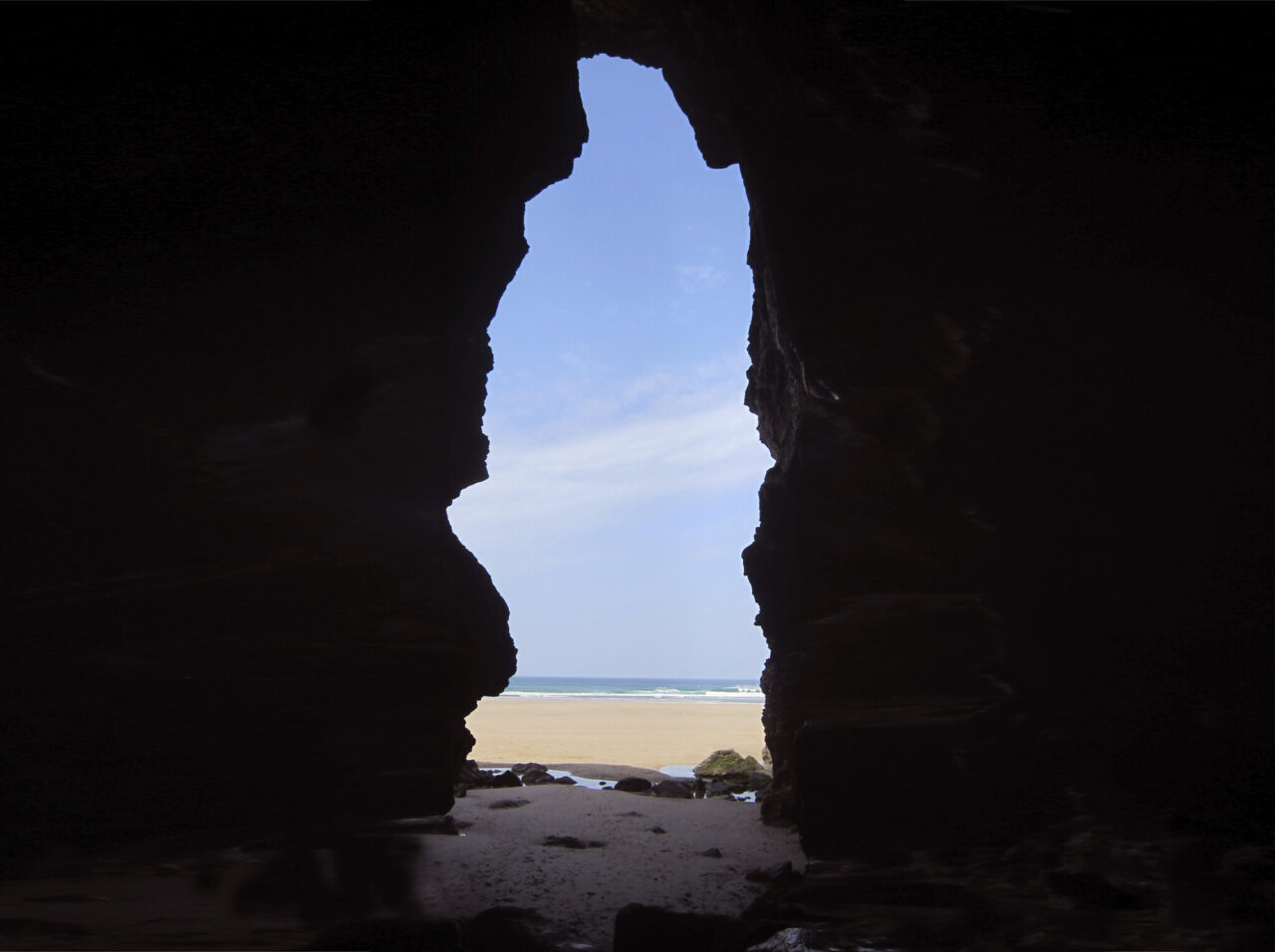 The mouth of a cave, showing the sky, sea and a beach beyond
