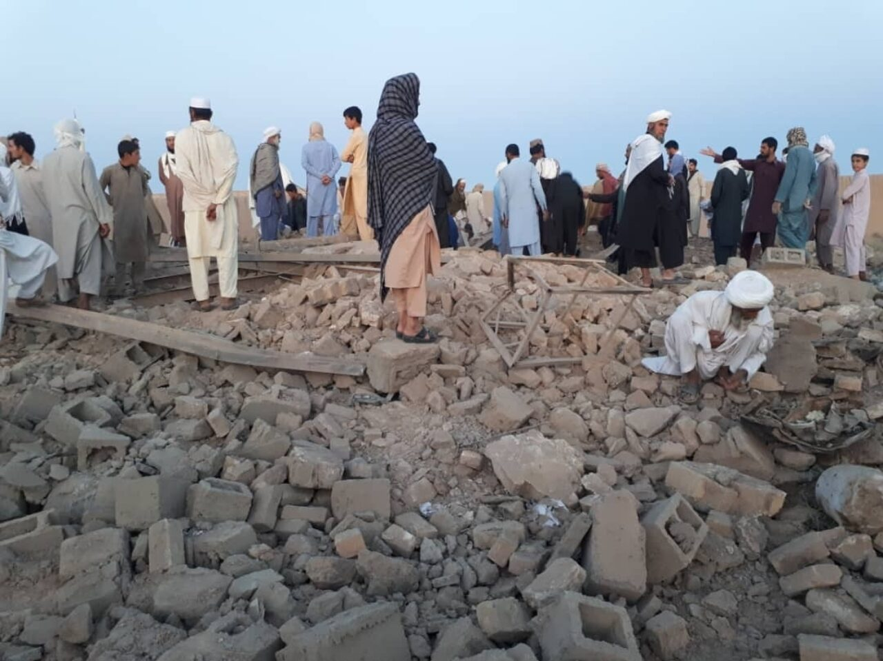 People stand on a levelled building at daybreak
